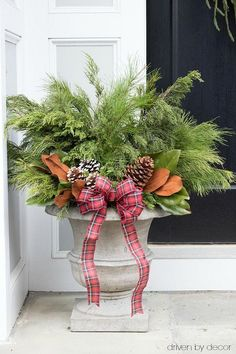 Christmas home tour - create festive Christmas / winter planters by adding greenery branches and pinecones to a pair of planters #christmas #decorating #decoratingideas #porch #planter