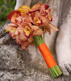 Brides.com:  Orange and green come together in a graceful bouquet of cymbidium orchids and calla lilies wrapped in a velvet ribbon, Beautiful Blooms.