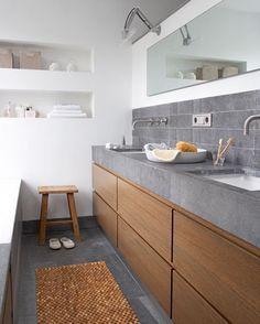 In deze badkamer is gekozen voor grote gebruiksoppervlakken. Achter de wand schuilt een douche en de mooie natuurlijke materialen zorgen voor een chique uitstraling.