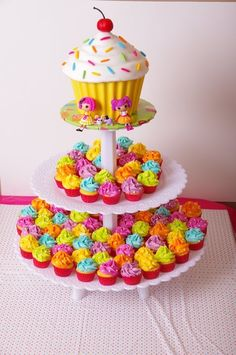 sweet-shoppe themed birthday cake and cupcakes with out the dolls and with a circled table and a tutu around the table this will look beautiful of course maybe changing the cupcake colors