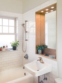 bright, upgrade to this small bathroom after it's reader remodel with white subway tile wrapping around the walls, a wall-hung sink, and inset wood-framed mirror over the sink