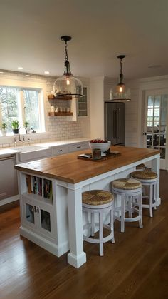"reclaimed barnwood island top, hand blown glass cloche pendant lights, white shaker cabinets with beveled glass extra large  cloche pendants from shades of light barnwood island top hood trim.and shelves from asbury woodcraft wolf 48"" range rohl faucet and pot filler"
