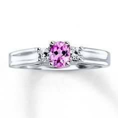 Cheerful and chic, this ring for her features an oval lab-created pink sapphire, complemented by a round lab-created white sapphire on each side. The ring is fashioned in sterling silver.