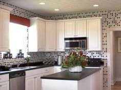 Beautiful polka dots kitchen wall paper with nice black granite table and white wooden storage