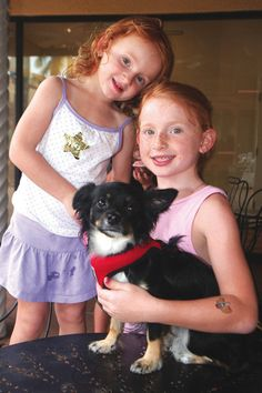 "Pawty time. Kamryn Samuel, left, and Averi Samuel with dog Ruby at the Tri County Humane Society's ""Paw-ty Time,"" which took place on Aug. 12 at The Shoppes at Village Pointe. (photo by Janis Bucher)"