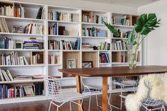 Comedor moderno y claro con mesa de madera de incienso (Deco Gallery), sillas Bertoia blancas (Manifesto) y biblioteca.