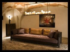 Designer : Tristan Auer: Long sofa with suspended tray of candles and brick arched ceilings