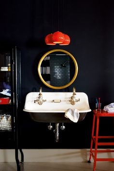 Black walls highlight the luxurious quality of brass and gold, and enhance the bright red accents