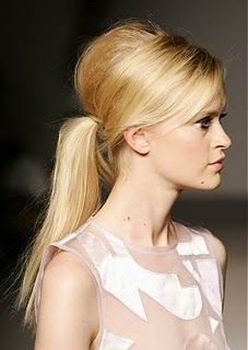 Retro Bump: Apply a golf ball size dollop of mousse to hair before blow-drying to add extra height at your roots. Make a deep side part, and tease the hair at your crown with a brush before slicking back into a low pony.