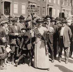 A Suffragette, wearing a sash and carrying a homemade sign, is surrounded by a crowd of men and boys. 1914.