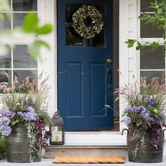 A pair of planters and a wreath in bloom.