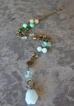 This necklace corresponds to the throat, heart, and root chakras and is made of a large aquamarine nugget, quartzite, green chrysoprase, green jade, prasiolite (green amethyst), copper czech glass, aqua chalcedony, pyrite, blue quartz glass, antique brass circles with antique brass chain.  The neckl...