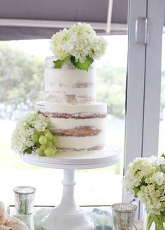 Rustic naked wedding cake with green hydrangeas