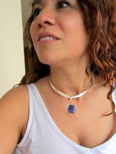 Tu piel es el marco más ideal, siempre. Colgante de ópalo azul, engarzado en hilo de plata formando unas sencillas volutas.