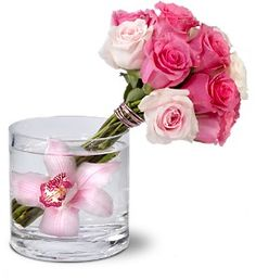 Celebrate a creative spirit with this striking floral arrangement of light and dark pink roses, tied with shimmering pink wire, and balanced in a glass vase that holds one perfect pink orchid. It's a unique gift for someone with exquisite taste.    A bouquet of hot pink and light pink roses – tied with pink aluminum wire – is delivered in a clear glass cylinder vase with a pink cymbidium orchid.