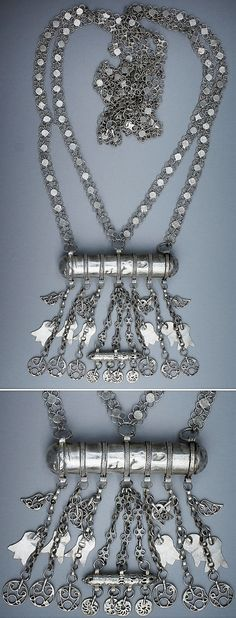 Kurdish amulet 'necklace' with an extremely long chain.  In fact, it is/was worn over the shoulder.  From southeastern Anatolia or Iraqi Kurdistan, ca. 1925.  Low silver or alloy cylindrical box (called 'nuska' or 'hamay'), hanging on a double quatrefoil chain.  Another small cylinder hangs underneath with many botehs, flower/hand shapes and circular ornaments. (Source: Lynn Ardent, Redmont, USA).