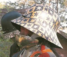 An example of a sallet with a unmovable visor of deep eye slits, common in 15th century. This is also an example of the being painted with designs and mottoes (background subject).