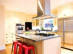 Paint the kitchen cabinets a light yellow. The shade creates a bright, fun feel. The paint the barstools red to add an exciting pop of color. Design by Erinn Valencich