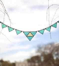 Add a bit of color to a drab window or brighten up any wall in a jiffy with the hanging of this sprightly stained glass garland. It's fashioned from handmade glass triangles, finished with silver-toned lead-free solder and hung from a hemp cord. Simply hang 'er up with small nails or hooks, and she's all set.