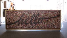 A reception desk, covered in buttons! by Jo Van der Linde of button candy I see me doing this with glitter or diamonds of some sort! Love the hello. Salon Reception Desk, Lobby Reception, Reception Counter, Office Reception, Reception Design, Reception Areas, Dance Studio Design, Desk Cover, Office Fit Out