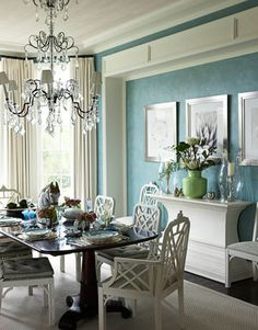 blue dining room design, white cane dining chairs, silk white drapes, crystal chandelier and sculptured white buffet, Turquoise blue green white dining room space colors.