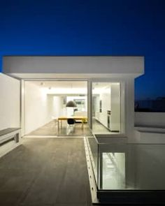 The barrier between indoors and outside is almost non-existent on the top level. Large, wide sliding doors connect the two spaces, allowing the home owners to effortlessly move between the two on long hot summer nights.  Modern Houses by MARLENE ULDSCHMIDT