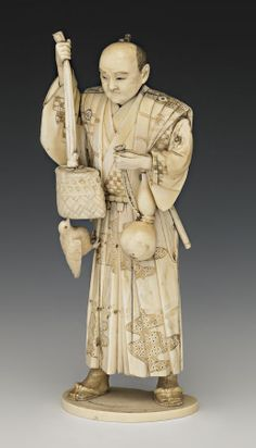 A sectional ivory figure, Meiji period, of a man clasping the rope of a double gourd in his left hand, the right holding up a long sash tied to a wicker basket and a bird perched on his robe below, incised detailing picked out in black 22.5 cm
