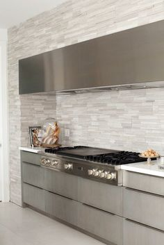 Gray kitchen with frameless gray cabinets paired with white quartz countertops and white linear backsplash. Kitchen features stainless steel dome range hood over high-end gas range.