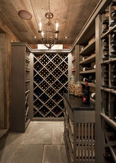 Basement wine cellar with rustic plank ceiling and stone pavers. Taupe built-in wine racks housing hundreds of bottles of fine wine. Basement wine room with exposed brick walls and taupe cabinets and taupe crown molding. Wine Cellar Basement, Home Wine Cellars, Wine Cellar Design, Wine Design, Plank Ceiling, Plank Walls, Ceiling Fan, Wine Cabinets, Italian Wine