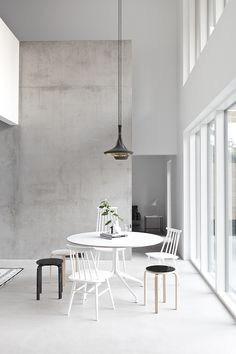Mismatched chairs in monochrome give a new spin to a meeting table - would work just as well at home around a dining table!