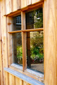 Bespoke larch shed constructed by Kevin Clark of Water Gems.  Rebar beds reflected in window.  Designed by Carolyn Grohmann, www.secretgardensdesign.co.uk