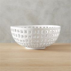 Shop basket bowl.   Handmade of porcelain that's fired, glazed, then fired again, freeform squares are handcut to reveal a graphic radius of tiny windows.  Offers a peek to the bread, fruit, napkins, or decor within—and just as striking on its own.