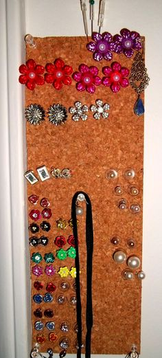 No-cost stud earring holder. Stuck to the wall with four pushpins, and drop earrings hung off of the pushpins.