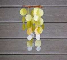Green/Yellow Capiz Chime.  Thin, hand-strung translucent capiz offer the color and sounds of spring. #Capiz are farmed in Indonesia and every bit is used. The pieces are carefully sorted, dried, sliced, shaped, sanded and dyed. Strung together with strong, invisible, nylon cord, the thin, flat translucent pieces provide luminous color.  #windchime #windchimes