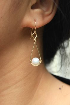 A pair of drop earrings featuring a white cultured freshwater pearl suspended from 14K gold filled or sterling silver wire. The earrings are hammered for textur