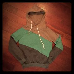 Asymmetrical hoodie. Size: S. Adorable asymmetrical hoodie. Tan, green, blue. Never worn/washed. Size: S. Tops Sweatshirts & Hoodies
