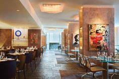Neutral stone floors, sourced from Ontario, offset the vibrant textured orange columns that serve as gallery space for pop-art paintings by Mr. Brainwash in Chef Daniel Boulud's first Toronto eatery, a contemporary space designed by Rosalie Wise Designs in the new Four Seasons Hotel Toronto.