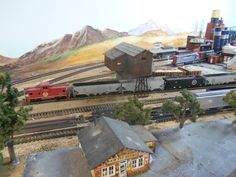 The west wall of the original layout section. Lots of touch up needed but hard for me to get to.  I had to SIT on the board to paint the mountains on the wall and can't do that anymore!