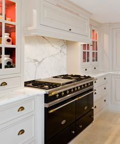 Love the glass cabinets on either side of this stove. Color and Lighting inside is Gorgeous. I like hood too if we don't go metal.