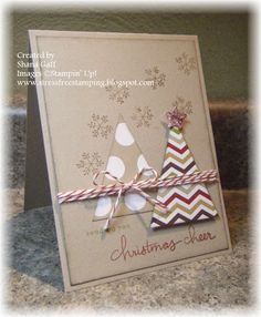 Triangle trees on kraft paper with baker's twine makes a rustic handmade Christmas card.  Snowflake stamps and inked edging on the top panel add the finishing touches.