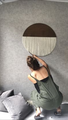 DIY wooden circular wall hanging with fringe hanging from it