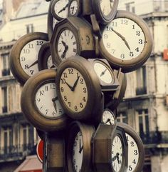 "created by the artist arman, this towering sculpture of stopped clocks tells the viewer about time. none of the faces shows the same display, as if to suggest that ""time stands still."" it's outside of the gare saint-lazare, the second-busiest train station in paris. @ebe porter"