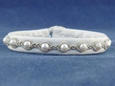 SwedArt B21-P Snowball Pearl, White Lambskin, Sterling Silver Button, Pewter and Silver Braids, XX-SMALL    6-1/4 (16 cm), Womens XXS for 5-3/4 wrist, 3/8 (9 mm) wide    Swedish LAPLAND JEWELRY has been popular in northern Europe for a long time but is now POPULAR ALL OVER THE WORLD. The bracelets are hard to find, though, and are usually sold in high-end fashion boutiques in major cities at prices that are two and three times the SwedArt prices. New trendy designs and colors i...