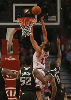 Joakim Noah #13 of the Chicago Bulls puts up a shot over James Johnson #52 and Thomas Robinson #0 of the Sacramento Kings at the United Center on October 31, 2012 in Chicago, Illinois.