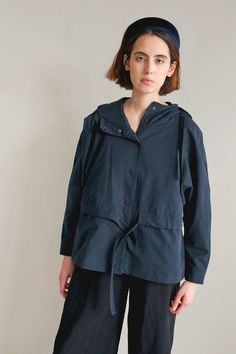 Short jacket with a hood on a high-collar. Reglan sleeves, finished in a cuff. On the waist height sewn-in tunnel with a belt, so you can tied the jacket. At the front, hidden under the tunnel, symmetrical pockets. Jacket lined, fastened with minimalist, metal snaps.