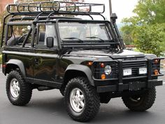 Land Rover Defender 90 Soft Top in Black with pull cable, fishing rack, surf board rack and utility lights.