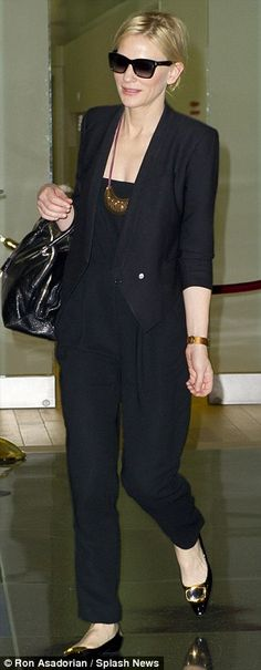 Travelling in style with black jumpsuit, accessorized to perfection with a statement necklace and classic black sunglasses