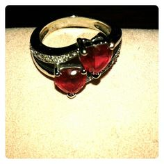 Beautiful Ruby heart ring Red ruby double heart ring. I love this ring, but I have so many. It's has silver stones on each side with two hearts across each other. I have received many compliments wearing this ring. It's a size 7, but fits like a 6.5. Jewelry Rings