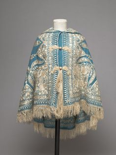 Child's cape, 1860-70, at the V & A Museum. Twilled peacock blue woollen cloth, embroidered in cream silk thread, with a cream tassel on the hood; Anglo-Indian (?).