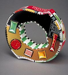 Bracelet |  Harriete Estel Berman. Daintes Bracelet.  Constructed entirely from recycled tin cans; the candy images and the outside edge are from a vintage, 1950's tin can. The top is metallic gold and black background.
